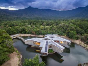 The bedroom wings, which are topped with photovoltaic panels, are cantilevered out over the lake.